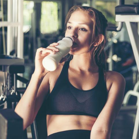 画像:トレーニングジムで、トレーニングウェアをきた女性がシェイカーに入ったプロテインを飲んでいる様子。