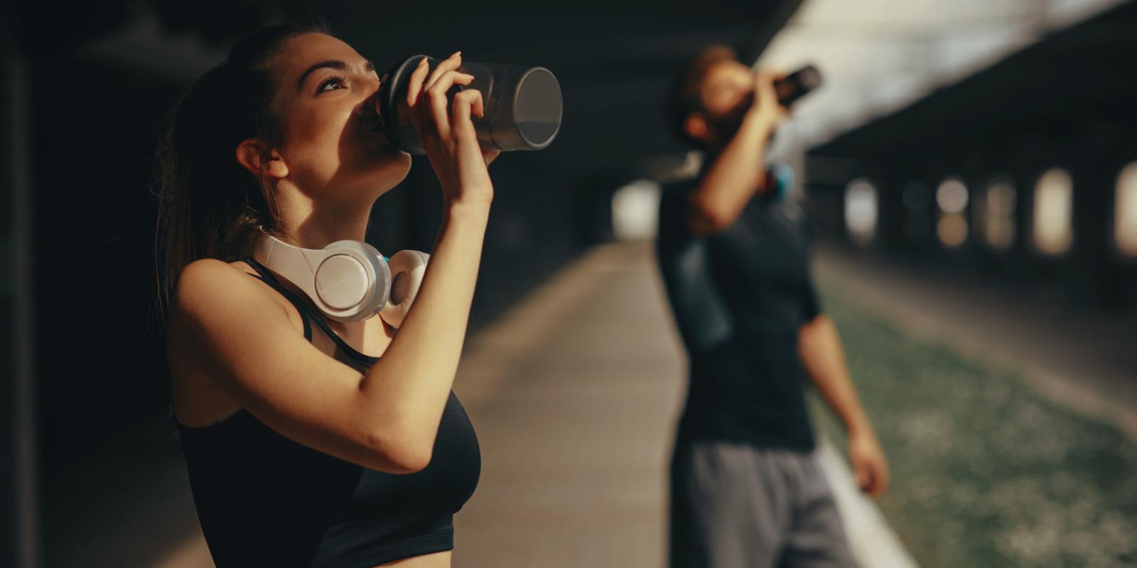 画像;タンクトップにヘッドホンを首にかけた女性、外でトレーニングの後、シェイカーに入ったプロテインを飲んでいる様子。