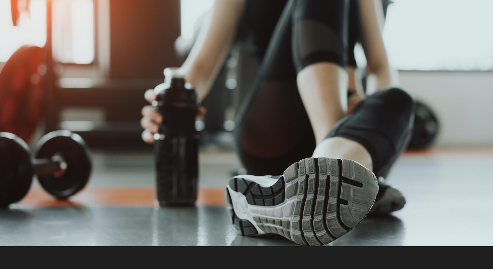 画像:ジムの室内でトレーニングした後、座ってプロテインを飲んでいる様子。